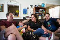 Andrew Morrison, Marilyn, 9, Chelsa and Miles, 10, lounge on the couch in their Grapevine home. (Ryan Michalesko/Staff Photographer)