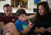 Marilyn Morrison, 9, explains to her parents, Andrew and Chelsa, how to use a function on a smartphone.(Ryan Michalesko/Staff Photographer)