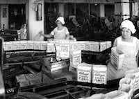 In this circa 1922 file photo provided by the Kellogg Co., factory employees pack Corn Flakes packages in Battle Creek, Mich.   (The Associated Press)