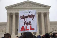 Pamela Yuen, with the American Association of University Women, holds a sign in favor of affirmative action outside of the Supreme Court in Washington.(File Photo/The Associated Press)