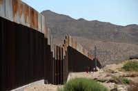 """<p></p><p>A Mexican family stands next to the border wall between Mexico and the United States, in Ciudad Juarez, Mexico.</p><p></p>(<p><span style=""""font-size: 1em; background-color: transparent;"""">Herika Martinez</span><br></p>/<p><span style=""""font-size: 1em; background-color: transparent;"""">AFP/Getty Images</span><br></p><p></p>)"""