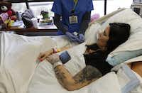 A nurse gives an injection to Roxanna Mayo as she lays in a hospital bed on April 8, 2015. (Rose Baca/The Dallas Morning News)