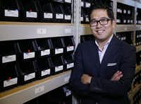 Paul Song, president of Cufflinks.com, stands in front of containers of hundreds of cufflinks the company designs for clients all over the world on Friday, November 7, 2014 in Dallas, Texas.  (David Woo/The Dallas Morning News) 11232014xBIZ(David Woo/Staff Photographer)