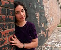 <p>Cora Cardona, co-founder and artistic director of Teatro Dallas, leans on a wall of the company's past location, which was damaged by a fire in November 1998.</p>(Staff/1999 File Photo)