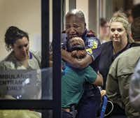 A DART (Dallas Area Rapid Transit) police officer receives comfort at Baylor University Hospital emergency room entrance on July 7, 2016 in Dallas, Texas. (Ting Shen/Staff Photographer)