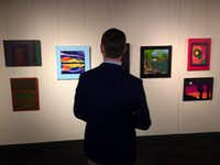 Dallas County Judge Clay Jenkins on Friday admired paintings at Dallas Love Field that were done by juveniles at Dallas County lockups. (Naomi Martin/Staff)