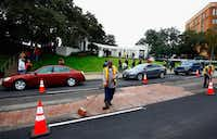 Dallas city workers repair the asphalt on Elm Street in Dealey Plaza as people visit Dealey Plaza on November 21, 2013.(Tom Pennington/Getty Images)