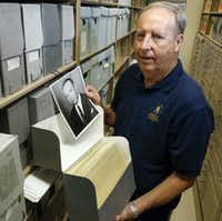 Retiree Leonard Davis, 70, volunteers in the Dallas Historical Society photo archives at Fair Park once a week. The photo he is holding is of John L. Patton Jr., a former civic leader and principal at Booker T. Washington High School.(Ron Baselice/Staff Photographer)