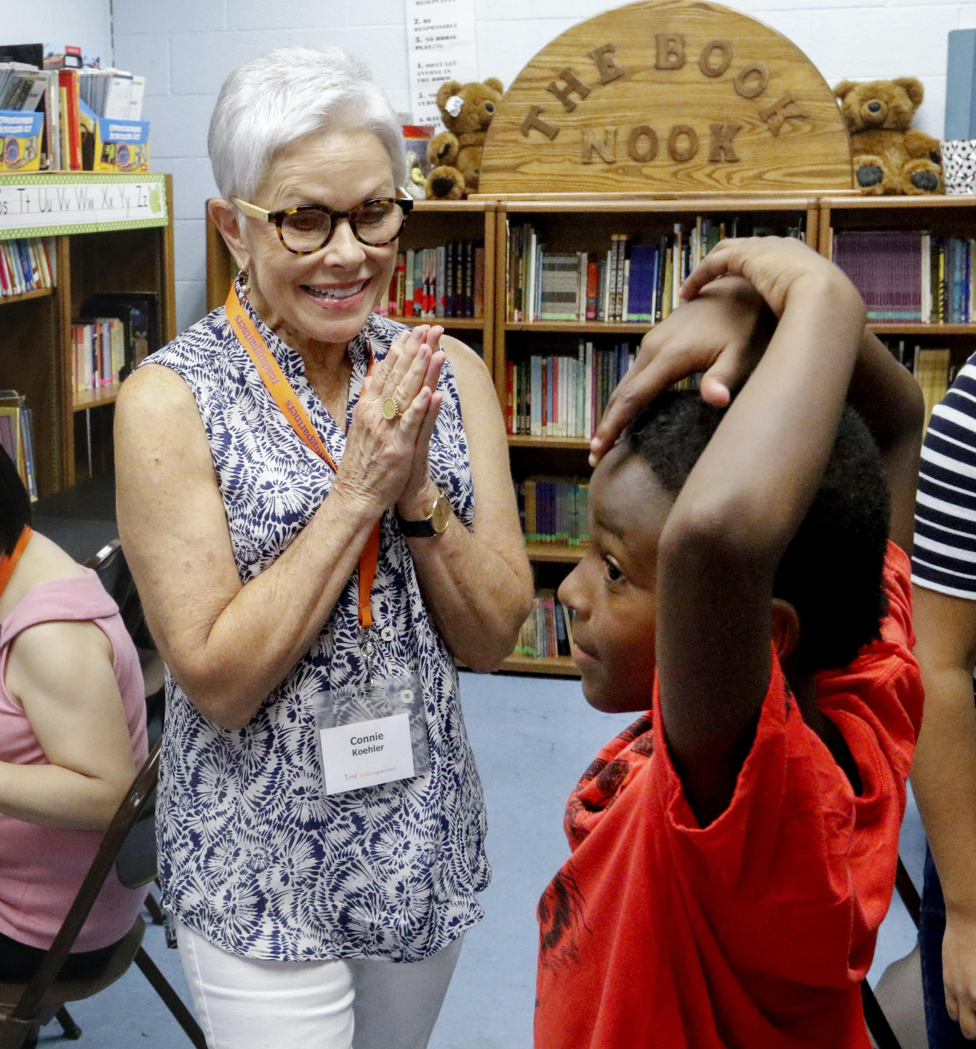 Connie Koehler, 65, a volunteer with Reading Partners, visits with Bradley Williams, 7, before their tutoring session at the Como Community Center in Fort Worth. (Ron Baselice/Staff Photographer)