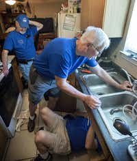 Charles Kownslar (far left) watches as fellow Plain-O Helpers team member Dwaine Finseth (middle) holds a new faucet fixture in place while Jack Mitchell secures it in Edward Perez's­ kitchen in Plano. (Robert W. Hart/Special Contributor)