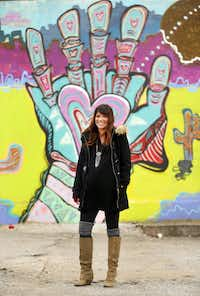 Artist Lesli Marshall poses in front of her mural <i>Cosmic Journey</i>. The piece, on the back side of Pecan Lodge, is part of the 42 Murals project in the Deep Ellum area of Dallas. (Tom Fox/The Dallas Morning News)