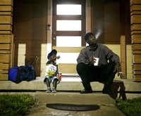 Joshua Miller and his son, Jordan, wait for the day care van to arrive. (Tailyr Irvine/Staff Photographer)