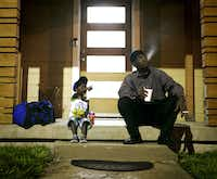 Joshua Miller and his son, Jordan, wait for the day care van to arrive.(Tailyr Irvine/Staff Photographer)