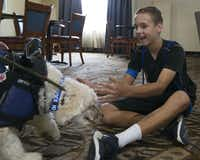 Brian Ellis welcomes Callie into his arms after months of being away from each other while she was trained to be a diabetic alert dog, at a hotel in Eastland. (Tailyr Irvine/Staff Photographer)