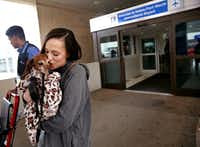 Donna Rosen kisses her dog Bobo while waiting for an Uber outside DFW International Airport. Bobo was missing for over a year before Rosen was able to track him down in Oregon. (Rose Baca/Staff Photographer)