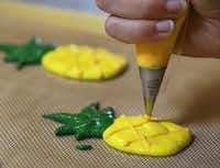 """<p><span style=""""font-size: 1em; background-color: transparent;"""">Baker Kelcie Feldotto first piped the pineapple macarons onto a reusable baking mat using yellow and green batter. Orange icing was piped on top for the crisscross design. Both sides go into the oven, then are sandwiched with piña colada-flavored filling. They sell for $4 each.</span></p>(Louis DeLuca/Staff Photographer)"""