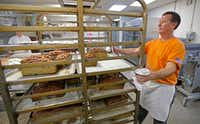 Cutshall pulls trays of freshly baked bread from the oven.(Jae S. Lee/Staff Photographer)