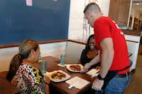 Corey Ahrens, 37, serves lunch to Regina Coter (left) and LaShamda Cole at Fish City Grill in Richardson on Tuesday, July 18, 2017. (David Woo/Staff Photographer)