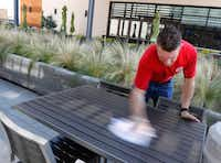 Corey Ahrens, 37, wipes off outdoor tables at Fish City Grill in Richardson, Texas, on Tuesday. He starts his day with a 45-minute commute, including two long walks and a five-minute train ride on DART. He works as key manager, server and bartender about 50 hour a week. (David Woo/Staff Photographer)