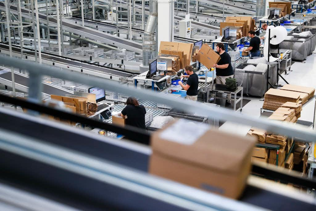 """In this May 17, 2017, photo, workers operate packaging stations that feed into an expansive system of conveyor belts connecting separate factory areas at a Festo distribution center in Mason, Ohio. """"None of these technologies work without the people,"""" said Carolin McCaffrey, head of Learning Center Midwest for Festo Didactics, which last year launched two-year apprenticeship programs in mechatronics.(John Minchillo/AP)"""
