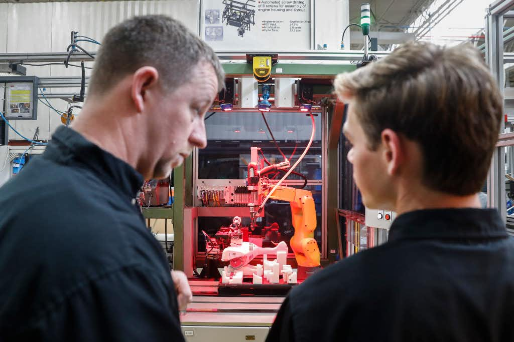 A.J. Scherman, 37, left, works with fellow apprentice Ryan Buzzy, 18, right, on a robotics control computer at a chainsaw assembly line at a Stihl Inc. production plant in Virginia Beach, Va.(John Minchillo/AP)