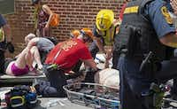 Injured people receive first aid after a car ran into a crowd of protesters in Charlottesville, Va., on Aug. 12. A vehicle plowed into a crowd of people Saturday at a Virginia rally where violence erupted between white supremacist demonstrators and counterprotesters, witnesses said. One person was killed.(Paul J. Richards/Agence France-Presse)