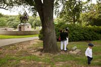 Matthew Chavez, 2, walks by as his mother, Miranda Taddei (in floral headwear), is readied before starting her marriage ceremony to Matthew Chavez near a statue of Confederate Gen. Robert E. Lee at Robert E. Lee Park in the Oak Lawn neighborhood of Dallas on Wednesday, Aug. 16, 2017. (Andy Jacobsohn/Staff Photographer)