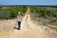 Amy Greer walks along the property line of her cattle ranch in Brady, Texas. Her family is working with city officials to prepare easements for a new water system. (Elizabeth Sims/News21)