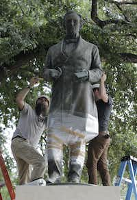 Workers wrap protective materials around a statue of Confederate President Jefferson Davis as they prepare to move the sculpture on the University of Texas campus, Sunday, Aug. 30, 2015, in Austin.(Eric Gay/AP)