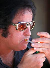 Elvis impersonator Phil Sneed lights a cigarette while performing on North Market Street by Wild Bill's Western Store in downtown Dallas. (Jae S. Lee/Staff Photographer)
