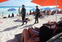 This file photo taken on January 18, 2017 shows Mexican Federal Police patrolling a beach in Cancun, Mexico, where a shooting occurred in a nightclub the day before. (STR/AFP/Getty Images)