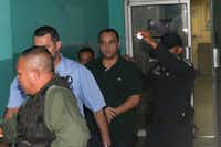 Roberto Borge, former governor of Mexico's state of Quintana Roo (center), is escorted by police after his extradition hearing in Panama City on Aug. 1. Borge was arrested for alleged corruption in connection with the sale of state properties worth hundreds of millions of dollars. Borge is the third ex-governor from the PRI detained this year on corruption allegations.(Arnulfo Franco/The Associated Press)