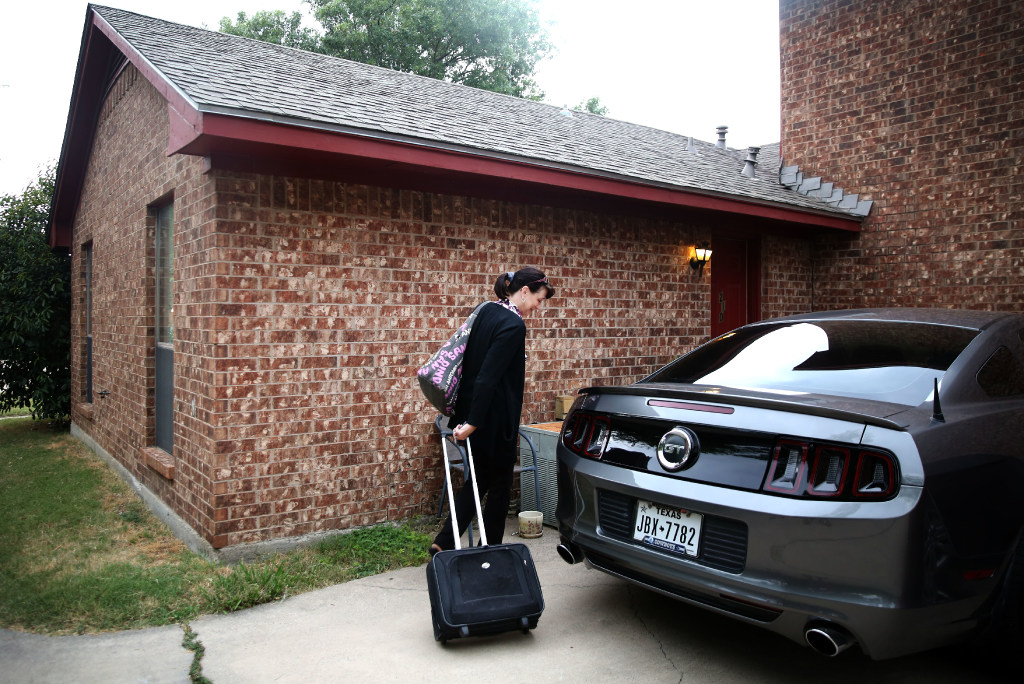 Dawn Humphrey hauls her luggage into her mother's home in Irving on  Aug. 2. Both she and her husband dropped out of college for medical reasons. They are still paying off more than $75,000 in student loans. Humphrey who lives in Waco and works in I