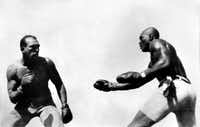 """In this photo taken July 4, 1910, Jack Johnson (right) fights """"Great White Hope"""" Jim Jeffries in Reno, Nev. A century ago Johnson reached the pinnacle of his career when he defeated Jeffries in what was billed as the Fight of the Century.(1910 File Photo/The Nevada Historical Society)"""