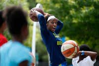 Dallas Wings forward Glory Johnson demonstrates passing the basketball to young kids. Throughout the season, kids have been able to practice passing, dribbling, shooting and defense skills at the Wings' basketball clinics.(Rose Baca/Staff Photographer)