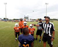Referee Fred Cox flipped the coin before the start of a youth football game between the Southwest Longhorns and Havoc at the Meadow Creek Park fields in DeSoto on Aug. 26.(Michael Ainsworth/Special Contributor)