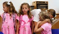 From left: Six-year-old triplets Emma, Chloe and Rosie Gilmore got hugs from their mother, Anna Gilmore, on the first day of school Monday at University Park Elementary School. (David Woo/Staff Photographer)