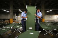 "Dallas Fire-Rescue recruits Marco Huerta (left) and Nathan Johnson help set up beds to house up to 5,000 Gulf Coast residents inside the ""mega shelter"" at the Kay Bailey Hutchison Convention Center in Dallas on Monday.(Rose Baca/Staff Photographer)"
