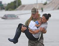 Houston SWAT officer Daryl Hudeck carried Catherine Pham and her 13-month-old son, Aidan, to safety after they were rescued Sunday.(Louis DeLuca/Staff Photographer)