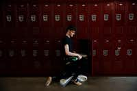 Dancer Lucas Dyson, a junior, kneels by his locker in-between classes.(Andy Jacobsohn/Staff Photographer)