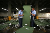 "Dallas Fire-Rescue recruits Marco Huerta (left) and Nathan Johnson help set up beds to house up to 5,000 Gulf Coast residents inside the ""mega shelter"" at the Kay Bailey Hutchison Convention Center in Dallas on Monday, Aug. 28, 2017. (Rose Baca/Staff Photographer)"