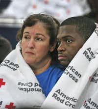 Displaced South Houston residents Oralia Guerra and Diamond Robinson huddle together to stay warm underneath Red Cross blankets at the George Brown Convention Center in Houston on Monday, Aug. 28, 2017, in the wake of Tropical Storm Harvey.(Louis DeLuca/Staff Photographer)