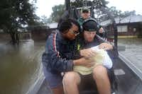 Shardea Harrison looks on at her 3 week old baby  Sarai Harrison being held by Dean Mize as he and Jason Legnon used his airboat to rescue them from their home after the area was inundated with flooding from Hurricane Harvey on August 28, 2017 in Houston, Texas. (Joe Raedle/Getty Images)