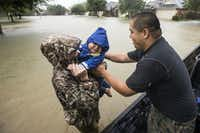 Wilfredo Linares reaches out for his baby, Mason, as they are evacuated from Grand Mission subdivision, as the water rises from heavy rains from Tropical Storm Harvey on Monday, Aug. 28, 2017, in Fort Bend County, Texas. (Brett Coomer/Houston Chronicle via AP)(Brett Coomer/AP)