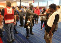 A man dressed as Batman shakes hands with people as they arrive at the Red Cross shelter at the George Brown Convention Center in Houston on Monday, August 28, 2017, as evacuees took shelter in the wake of Hurricane Harvey. (Louis DeLuca/Staff Photographer)