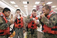 <p>From left: Pfc. Victor Ochoa, Spc. Edgar Duarte, Spc. James Sego and Pfc. Emmit Morgan devour brisket sandwiches at a Buc-ee's convenience store in use as a staging area for evacuation operations in Katy.&nbsp;</p>(Alyssa Schukar/The New York Times)