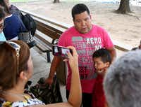 Jose Banda, an evacuee from Dickinson, Texas, speaks to the media with his son Justin Banda, 7, after arriving at the mega-shelter outside the Kay Bailey Hutchison Convention Center in Dallas on Tuesday, Aug. 29, 2017. (Rose Baca/Staff Photographer)