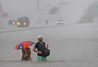 Motorists stranded in the flooding on  Loop 610 south near the Post Oak exit in Houston made their way to higher ground in the floodwaters, as rain from Hurricane Harvey battered the city on Sunday.(Louis DeLuca/Staff Photographer)