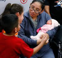 Nora Uribe holds her newborn baby daughter, Ximena, with her children, Antonio, 4, and Narale, 7, looking on at Medical City Plano. (David Woo/Staff Photographer)