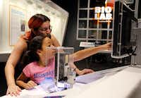 Janet Rodriguez and her daughter Sylvia Rodriguez, 9, of Spring check out an exhibit at the Perot Museum of Nature and Science.(Vernon Bryant/Staff Photographer)